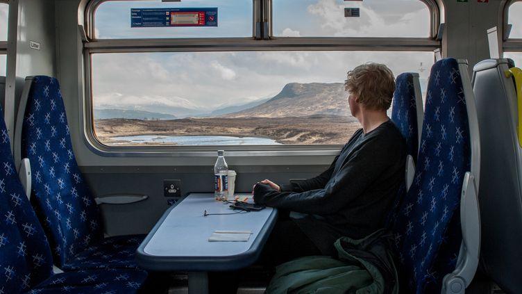 Un voyageur observe un paysage écossais depuis la fenêtre d'un train entre Glasgow et Mallaig, le 5 avril 2019. (LAURENT COUSIN / HAYTHAM PICTURES-REA)