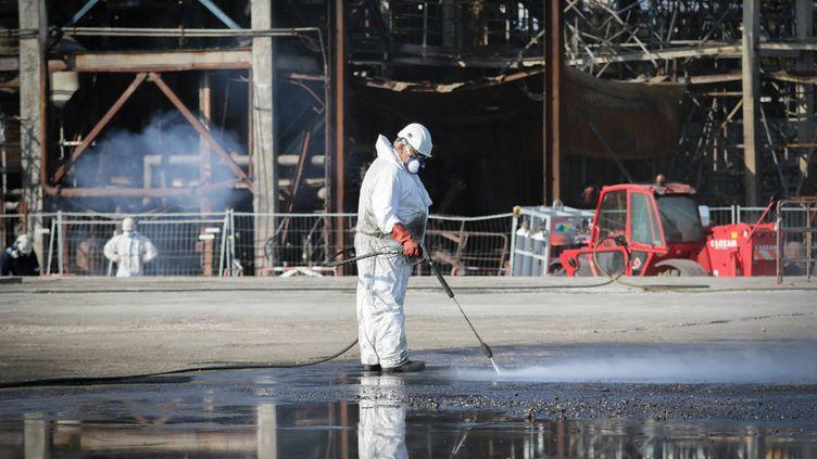 Un homme nettoie l'usine Lubrizol à Rouen (Seine-Maritime), le 18 septembre 2020, un an après l'incendie. (LOU BENOIST / AFP)