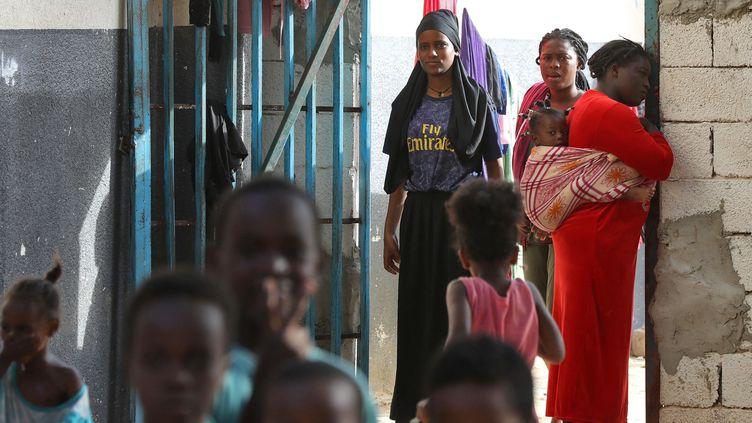 Des migrants africains regroupés dans un camp de fortune dans une banlieue de Tripoli, le 11 octobre 2021. (MAHMUD TURKIA / AFP)