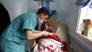 Dans un hôpital de Sanaa, au Yémen, un médecin s'occupe d'une patiente suspectée d'être atteinte du choléra, lundi 15 mai 2017. (MOHAMMED HUWAIS / AFP)