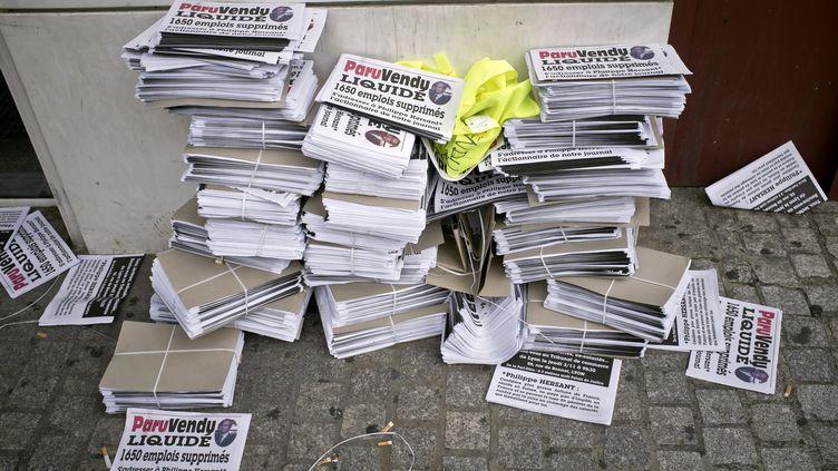 """Des faux exemplaires du """"Paru Vendu"""", le 3 novembre 2011 devant le tribunal de commerce de Lyon, où a été prononcée la liquidation judiciaire de son éditeur, la Comareg, et d'Hebdoprint, son centre d'impression. (JEAN-PHILIPPE KSIAZEK / AFP)"""