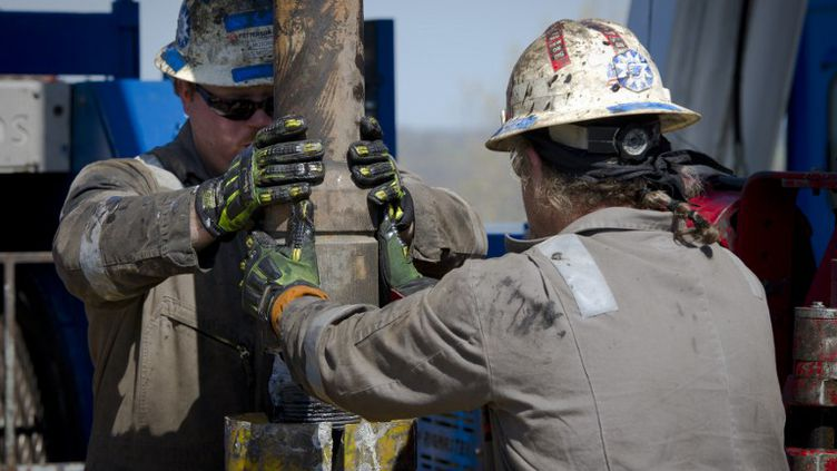 Des employés de Consol Energy remplacent une pièce sur une plate-forme de forage exploitant du gaz de schiste à Waynesburg, en Pennsylvanie (Etats-Unis), en avril 2012. (MLADEN ANTONOV / AFP)
