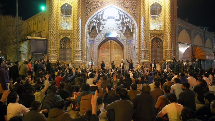 Des fidèles sont rassemblés devant les portes closesdu sanctuaire deFatima Massoumeh,àQom, en Iran, le 16 mars 2020.Mi-mars, les autorités iraniennes ont annoncé la fermeture de quatre importants lieux saints, dont le sanctuaire deMachhad, première ville sainte chiite d'Iran, pour lutter contre lecoronavirus. (MEHDI MARIZAD / AFP)