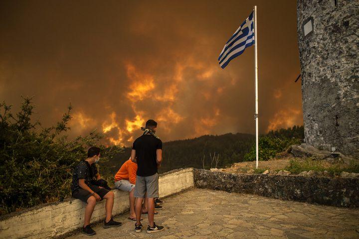 Les résidents locaux regardent l'incendie de forêt s'approchant du village de Gouves, sur l'île d'Eubée (Grèce), le 8 août 2021. (ANGELOS TZORTZINIS / AFP)