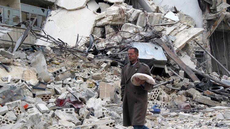 Un homme transporte du pain devant un batiment en ruines d'Alep (Syrie), dimanche 2 février 2013. (MOHAMMED AL-KHATIEB / AFP)