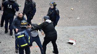 Alexandre Benalla (à droite), Vincent Crase (à gauche) et plusieurs policiers autour d'un jeune homme,le 1er-Mai à Paris. (NAGUIB-MICHEL SIDHOM / AFP)