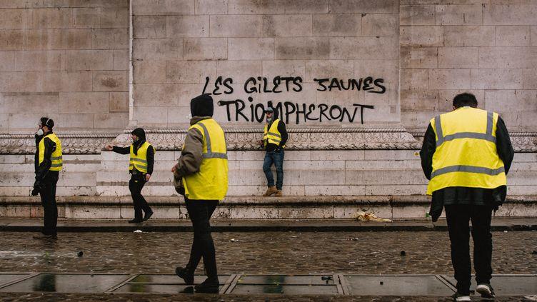 """Des """"gilets jaunes"""" devant l'Arc de triomphe, à Paris, le 1er décembre 2018. (SIMON GUILLEMIN / HANS LUCAS / AFP)"""