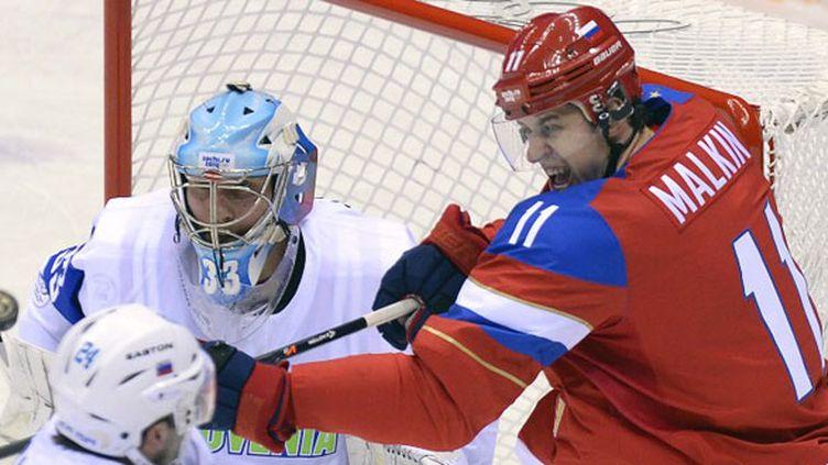 Malkin, auteur du deuxième but de son équipe, aux prises avec la défense slovène