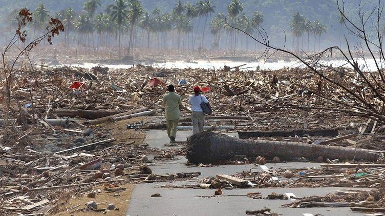 Des réfugiés indonésiens marchent sur une route jonchée de débris, le 9 janvier 2005, après le tsunami. (CHOO YOUN-KONG / AFP)