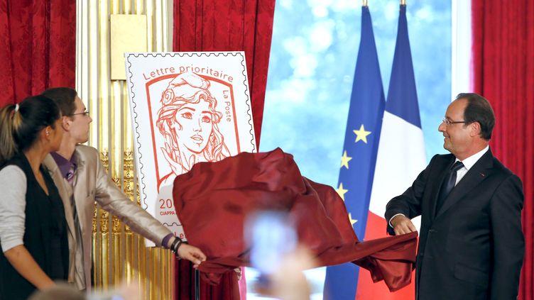 Le président François Hollande révèle le nouveau timbre Marianne, le 14 juillet 2013 à l'Elysée. (FRANCOIS MORI / AFP)