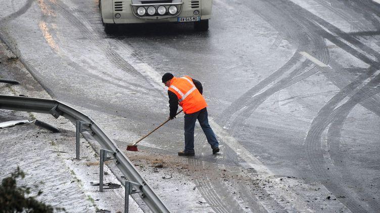 Un agent d'entretien des routes intervient après un accident sur la RN11 près de Ferrières, entre La Rochelle et Niort. (XAVIER LEOTY / AFP)