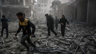 Des habitants et secouristes cherchent des survivants après des bombardements du régime syrien sur la Ghouta orientale, le 20 février 2018 à Sakba, en Syrie. (KHALED AKASHA / ANADOLU AGENCY / AFP)