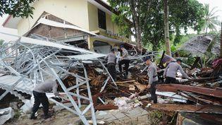 Des policiers indonésiens recherchent des survivantsaprès le passage d'un tsunami,à Carita (Indonésie), le 24 décembre 2018. (SONNY TUMBELAKA / AFP)
