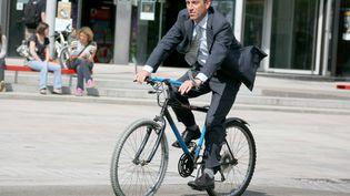 Un homme en costume-cravate se rend au travail en vélo. (MAXPPP)