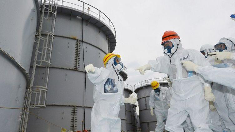 Le gouverneur de la préfecture de Fukushima, Yuhei Sato (casque orange), inspecte les réservoirs d'eau contaminée de Fukushima (Japon), le 15 octobre 2013. (JAPAN POOL / JIJI PRESS)