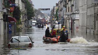 Des secours se portent en aide aux sinistrés de Nemours (Seine-et-Marne), le 1er juin 2016. (DOMINIQUE FAGET / AFP)