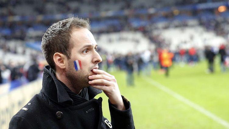 Un supporter français se fige sur la pelouse du Stade de France en apprenant que des attaques ont frappé la région parisienne. (CHRISTOPHE ENA/AP/SIPA / AP)