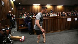 L'athlète paralympique Oscar Pistorius quitte ses prothèses et marche sur ses moignons, lors de son procès à Pretoria (Afrique du Sud), le 15 juin 2016. (SIPHIWE SIBEKO / REUTERS)