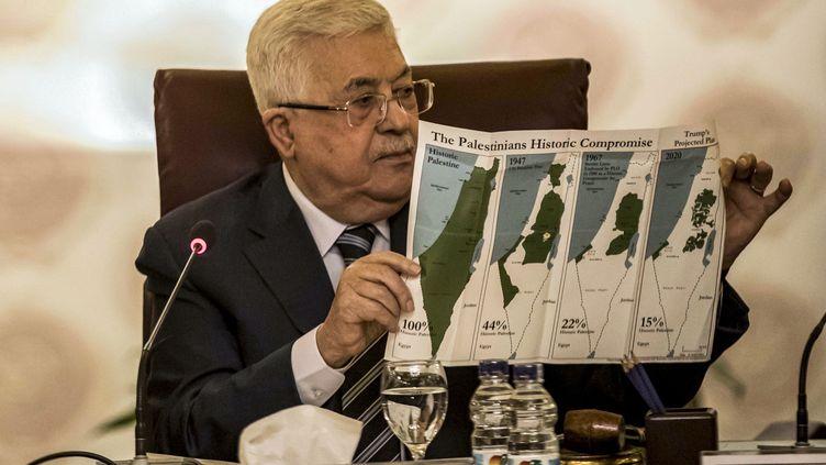 Le président palestinien, Mahmoud Abbas, tenant une carte de l'évolution des frontières des territoires palestiniens, le 1er février 2020, au Caire (Egypte). (KHALED DESOUKI / AFP)