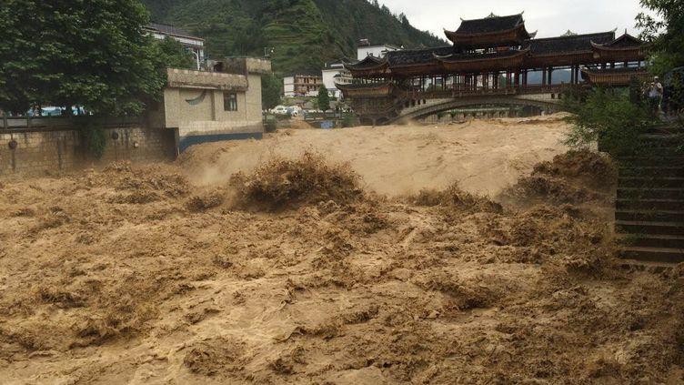 Un pont presque submergé par une inondation dans la province du Guizhou, dans le sud de la Chine, le 27 mai 2015. (ZHAO HUI / IMAGINECHINA / AFP)