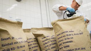Un inspecteur du bureau vétérinaire et d'importation du port de Hambourg (Allemagne) ferme un sac de sésame d'Inde après le prélèvement d'un échantillon, le 11 septembre 2018. (CHRISTIAN CHARISIUS / DPA / AFP)