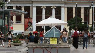 """Des passants sur une place à Athènes, le 29 juin 2015, à proximité d'un appel à voter """"non"""" (Oxi) au référendum sur les conditions du plan d'aide à la Grèce, dimanche 5 juillet, inscrit sur un banc. (AYHAN MEHMET / ANADOLU AGENCY/AFP)"""