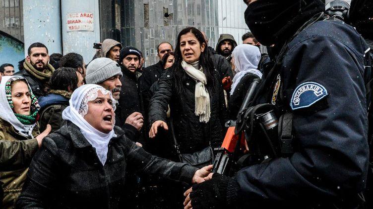 31 Décembre 2015 à Diyarbakir dans la région à forte population kurde de Turquie. Des femmes devant des policiers turcs. Le couvre feu imposée dans la région depuis le 2 décembre a été levé. Il témoigne de la tension qui règne entre le régime d'Erdogan et la population kurde qui a voté pour le parti d'opposition HDP. Selon ce parti, 56 civils ont été tués durant ce couvre feu.«Contrairement aux affirmations selon lesquelles ils s'agirait de garantir la paix et la sécurité, les autorités créent la peur et la terreur parmi les gens, tuant sans compter des civils et détruisant l'héritage culturel», a affirméle HDP. (ILYAS AKENGIN / AFP)