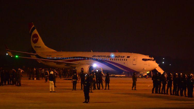 Des forces de sécurité bangladaises montent la garde près de l'avion ayant subi une tentative de détournement, le 24 février 2019, à Chittagong (Bangladesh). (STR / AFP)