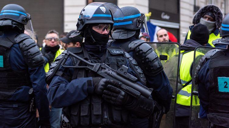 """Un policier tient un lanceur de balles de défense, le 29 décembre 2018, lors d'une manifestation des """"gilets jaunes"""", sur les Champs-Elysées à Paris. (KARINE PIERRE / HANS LUCAS / AFP)"""