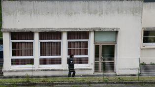 Une policière devant l'école maternelle Jean Perrin d'Aubervilliers (Seine-Saint-Denis), où un enseignant a été agressé à l'arme blanche, le 14 décembre 2015. (JACQUES DEMARTHON / AFP)