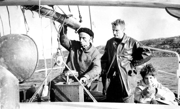 """Henry de Monfreid (G) accompagné à la poupe de son voilier l'""""Obok"""" de son fils Daniel (C) et de son petit fils Guillaume (D), le 17 avril 1962.  (AFP)"""
