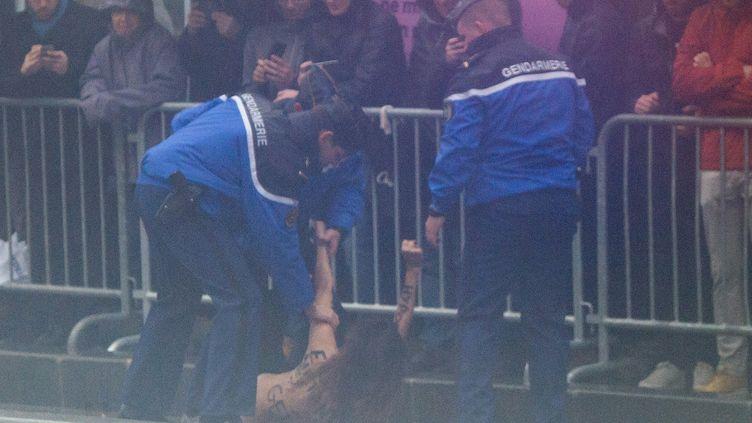 Interpellation d'une des trois Femen qui ont perturbé le passage du convoi du président américain sur l'avenue des Champs-Elysées, à Paris, le 11 novembre 2018. (SAUL LOEB / AFP)