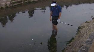 """Le golfeur Jean Van de Velde, pieds nus dans un ruisseau pour """"sortir"""" sa balle lors du 18e trou au British Open 1999. (CAPTURE D'ÉCRAN YOUTUBE)"""