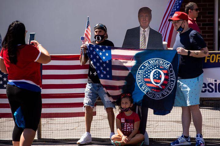 Des partisans du mouvement complotiste QAnon posentautour d'unereprésentation en carton de Donald Trump le 20 août 2020 à Old Forge(Etats-Unis), lors de la campagne présidentielle. (DAN RAINVILLE VIA IMAGN CONTENT /SIPA / AFP)