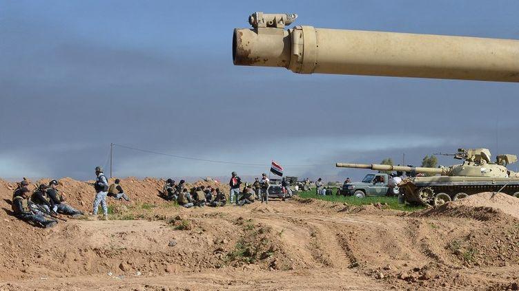 Des combattants irakiens des forces pro-gouvernementales prennent position à Al-Alam, au nord-est de Trikrit, le 8 mars 2015. (YOUNIS AL-BAYATI / AFP)