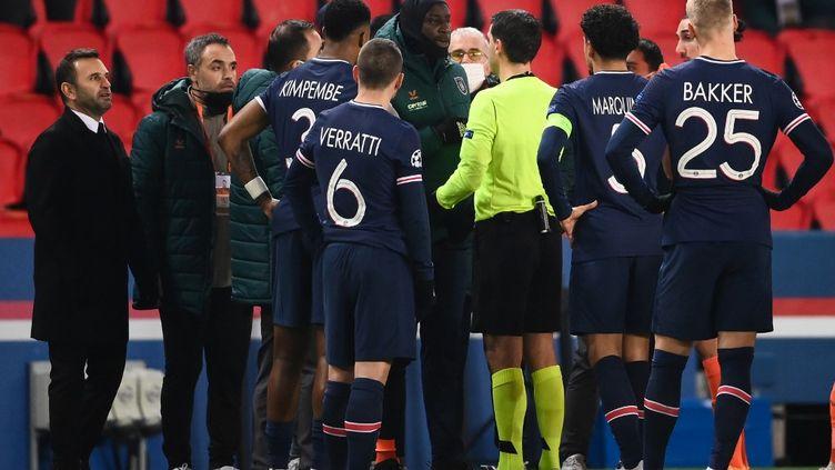 Entouré de joueurs parisiens, Demba Ba demande des explications à l'arbitre après des soupçons d'insultes racistes venues que quatrième arbitre. (FRANCK FIFE / AFP)
