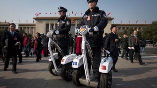 Pour circuler l'immense place Tiananmen, où se trouve le Palais de l'Assemblée du peuple, les policiers chinois sont munis de segways. (ED JONES / AFP)