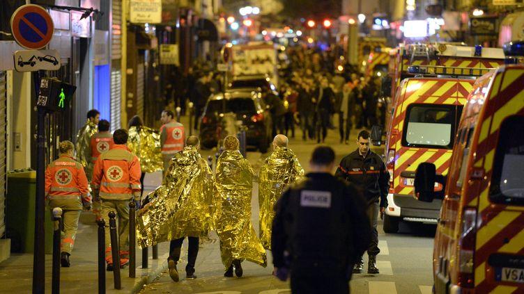 Des rescapés sous des couvertures de survie de l'attentat du Bataclan à Paris, le 13 novembre 2015, entourés par des secouristes. (MIGUEL MEDINA / AFP)