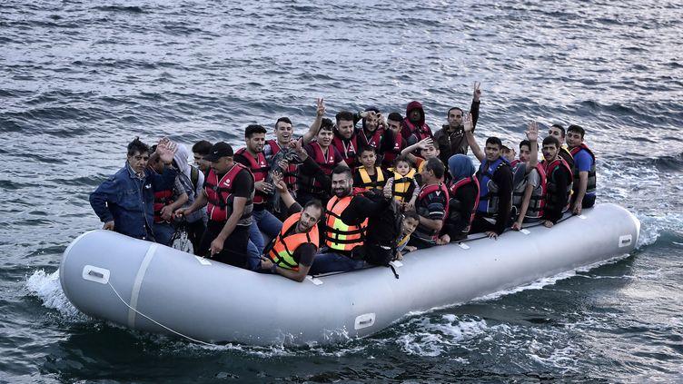 Des migrants syriens arrivent sur l'île grecque de Lesbos à bord d'un canot pneumatique, le 18 juin 2015. (LOUISA GOULIAMAKI / AFP)