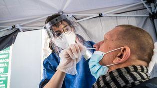 Une infirmière pratique un test antigénique pour dépister le Covid-19, à Paris, le 18 novembre 2020. (VOISIN / PHANIE / AFP)