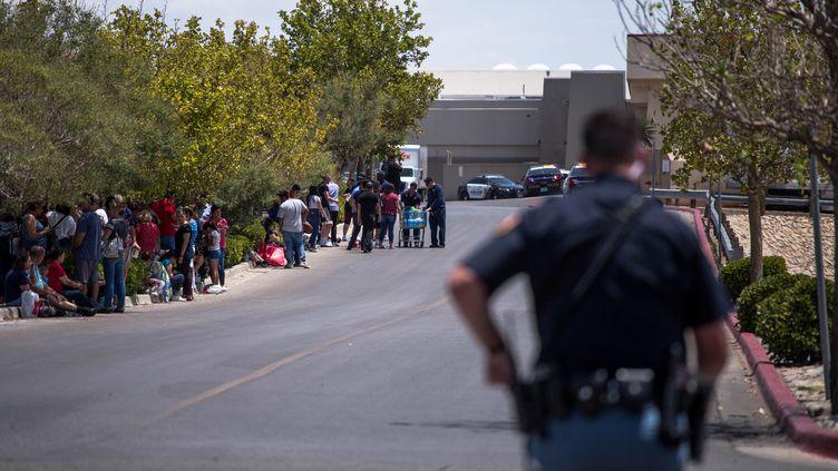 Des personnes évacuéesréunies en face du parking d'un hypermarché Walmart où un homme a ouvert le feu, le 3 août 2019, à El Paso (Texas, Etats-Unis). (JOEL ANGEL JUAREZ / AFP)