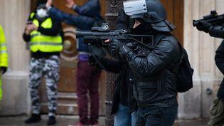 """Un policier fait usage de son LDB, lors d'une manifestation parisienne des """"gilets jaunes"""". (ALEXIS SCIARD  / MAXPPP)"""