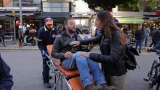Un blessé est évacué après l'attaque d'un bar, le 1er janvier 2016, à Tel-Aviv (Israël). (DANIEL BAR ON / AFP)