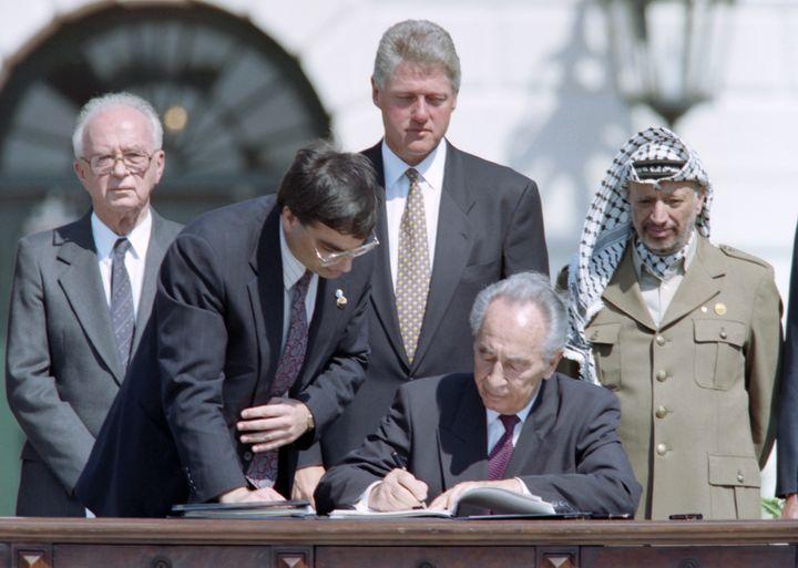 Shimon Peres lors des accords d'Oslo, le 13 septembre 1993, devant leleader palestinien Yasser Arafat,le Premier ministre Yitzhak Rabin et leprésident américainBill Clinton. (J. DAVID AKE / AFP)