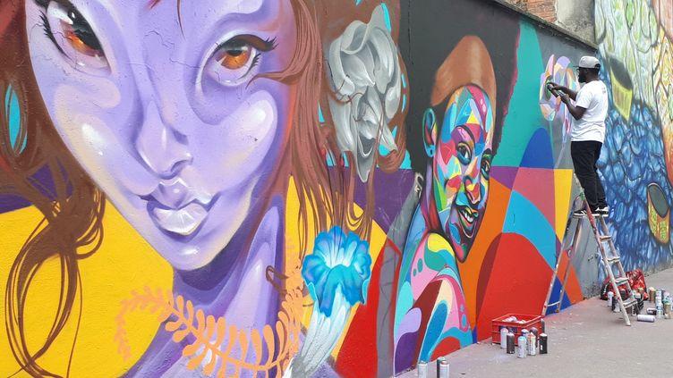 """Un street artiste lors de la réalisation d'un graph, le 9 juin 2019, rue Germaine Tailleferre à Paris pour le festival """"Ourcq living colors"""". Photo d'illustration. (STÉPHANIE BERLU / RADIO FRANCE)"""