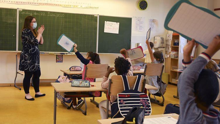 Une enseignante et ses élèves dans une école de Strasbourg (Bas-Rhin), le 22 juin 2020. (FREDERICK FLORIN / AFP)