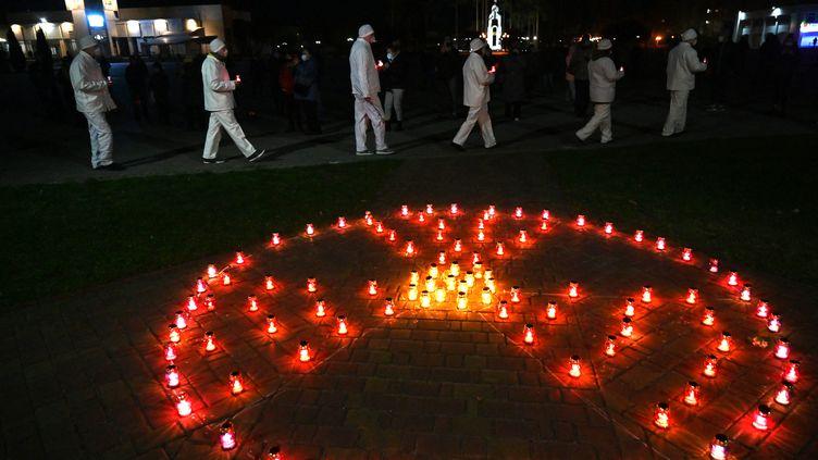 Des employés de la centrale de Tchernobyl participent le 25 avril 2021, à une cérémonie commémorative de l'accident du 26 avril 1986. (SERGEI SUPINSKY / AFP)