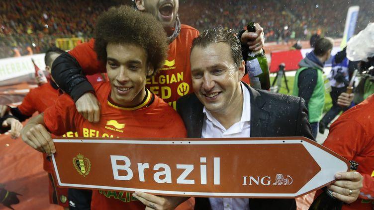 Le milieu belge Axel Witsel (G) et le sélectionneur Marc Wilmots (D) fêtent la qualification de l'équipe pour la Coupe du monde au Brésil, au Stade du Roi-Baudouin, à Bruxelles, le 15 octobre 2013. (FRANCOIS LENOIR / REUTERS)
