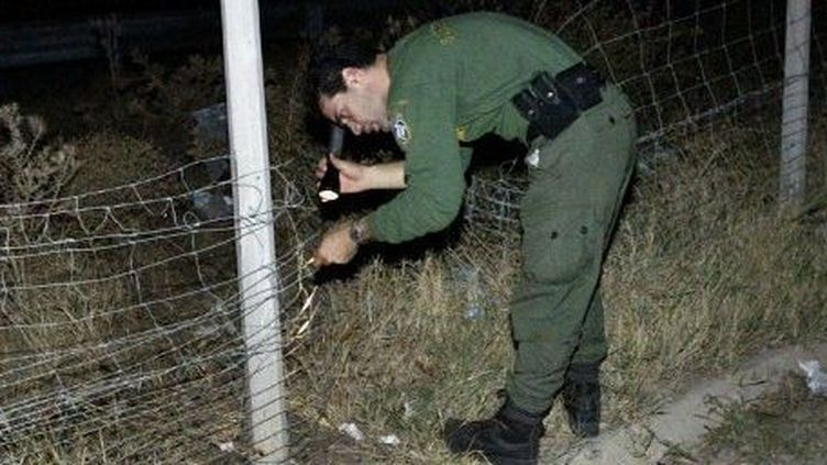 Un garde-frontière grec contrôle la clôture entre la Grèce et la Turquie, sur le fleuve Evros. Une barrière destinée à empêcher l'immigration en Grèce, porte d'entrée de l'espace Schengen. (AFP/FAYEZ NURELDINE)