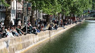 De jeunes Parisiens se réunissent le long du canal Saint-Martin, le 11 mai 2020 à Paris, à l'occasion de la première journée de déconfinement. (SAMUEL BOIVIN / NURPHOTO / AFP)